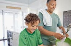 Dad and son doing dishes in kitchen   Hero Images/Getty Images