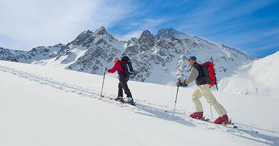 Two hikers climbing a mountain covered in snow