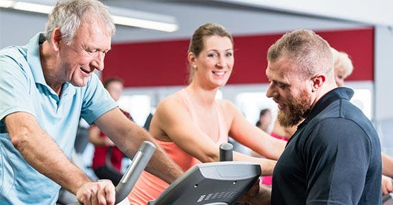 Man on workout machine as trainer looks on