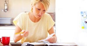 Woman budgeting in her kitchen © iStock