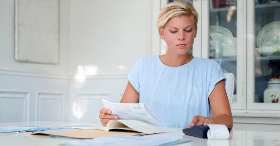 Woman at her kitchen table calculating bills © iStock