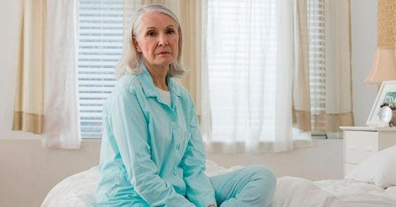 Sad senior woman sitting on bed | Image Source/Getty Images