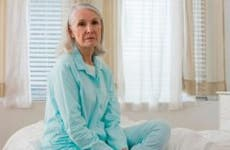 Sad senior woman sitting on bed   Image Source/Getty Images