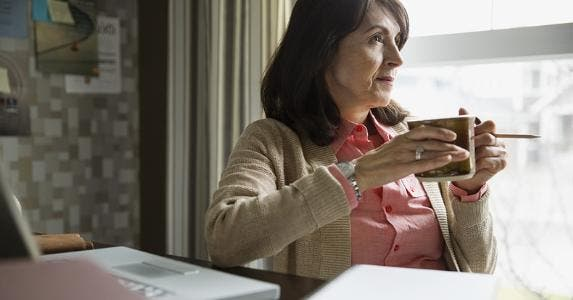 Older woman holding coffee mug | Hero Images/Getty Images
