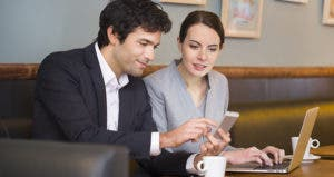 Professional couple looking at iPhone while searching on laptop © Ldprod/Shutterstock.com