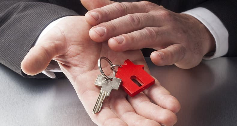 Businessman hands holding key with house keychain © STUDIO GRAND OUEST/Shutterstock.com
