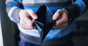 Man in blue striped sweater holding empty wallet © Champion studio/Shutterstock.com
