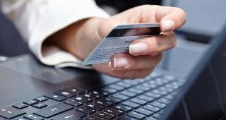Close-up of woman holding credit card near laptop © Denis Vrublevski/Shutterstock.com