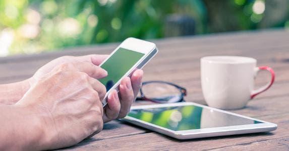 Using mobile and tablet outside at table © LittleStocker/Shutterstock.com