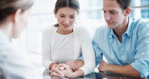 Young couple looking at paperwork, holding hands © iStock