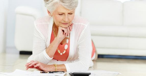 Woman using her calculator at home © iStock