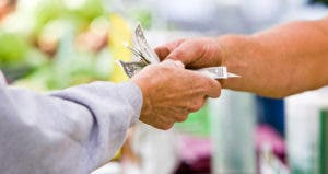 Male customer handing cash to store employee
