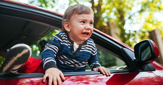 Crying baby hanging out of car window