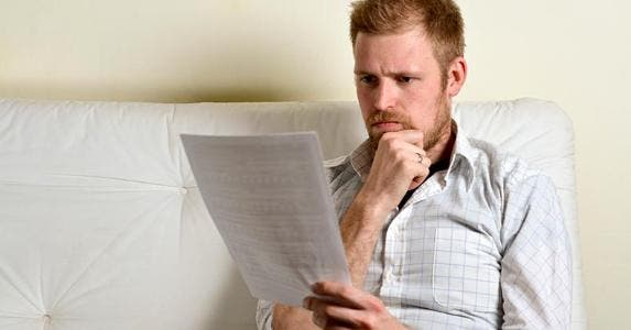 Serious young man reading paperwork © iStock