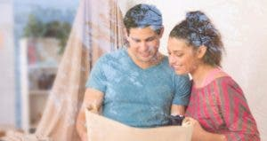 Couple indoors smiling at plans, reflection of trees on window | iStock.com/Pamela Moore