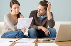 Stressed young couple going over paperwork and bills   Image Source/Getty Images
