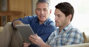 Adult son and father browsing tablet computer | Richard Drury/DigitalVision/Getty images
