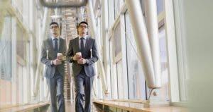 Young employee walking along glass corridor | Hero Images/Getty Images