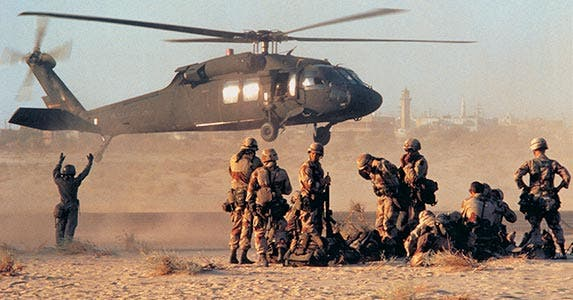 Military members standing as a helicopter lands nearby