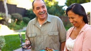 Older couple barbecueing in their backyard, laughing