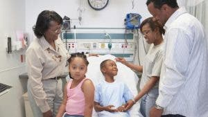 Family visiting young boy in hospital | ERproductions Ltd/Getty Images