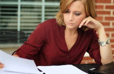 Woman writing and reading paperwork © Charlotte Purdy/Shutterstock.com