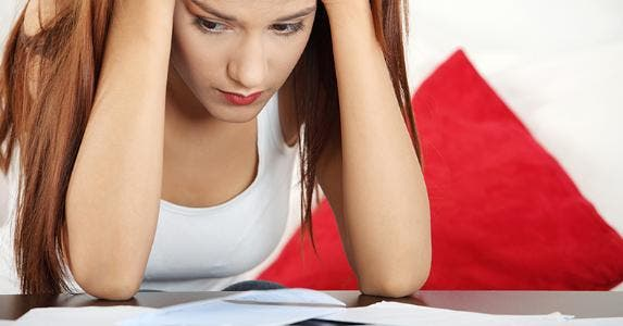 Young woman stressed over bills © Piotr Marcinski/Shutterstock.com
