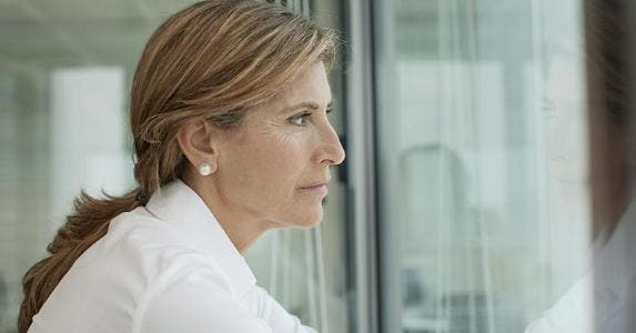 Serious woman looking out of window | PhotoAlto/Antoine Arraou/Getty Images