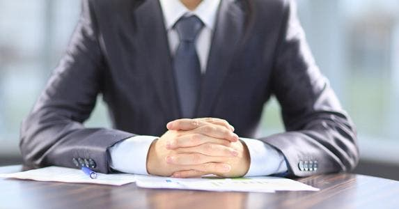 Businessman with hands folded on desk © YURALAITS ALBERT/Shutterstock.com