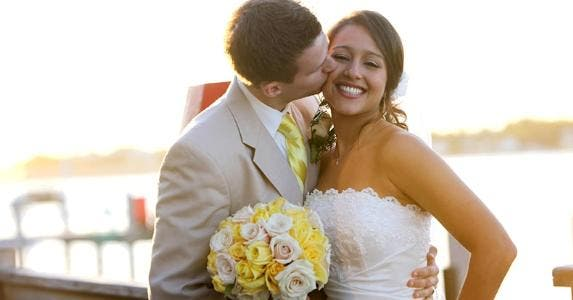 Groom kissing bride's cheek © iStock