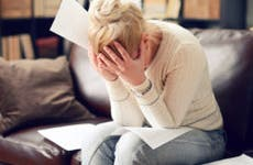 Overwhelmed, facepalming woman with paperwork