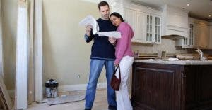 Couple reading paperwork in the middle of kitchen renovation