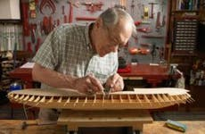Man working on model boat | Neil Beckerman/Getty Images