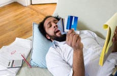 Man laying on the couch looking at his credit cards © iStock