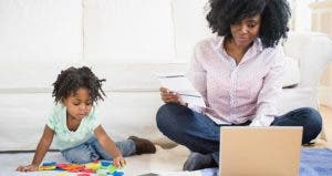Mom browsing laptop, sitting on the floor with playing toddler © JGI/Jamie Grill/Shutterstock.com