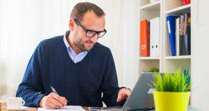 Man dressed in a shirt and sweater working in his home office © Jakub Zak/Shutterstock.com