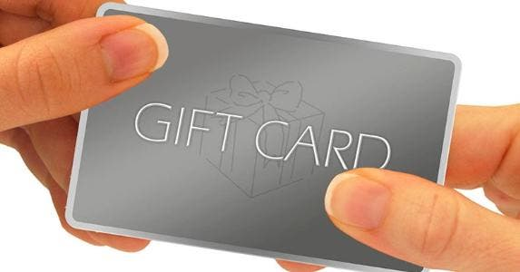 Woman holding gift card © ARENA Creative/Shutterstock.com