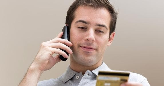 Man talking on cellphone while holding credit card © LDprod/Shutterstock.com
