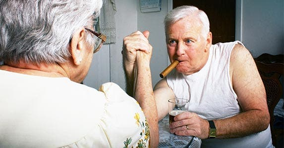 Two older men arm wrestling