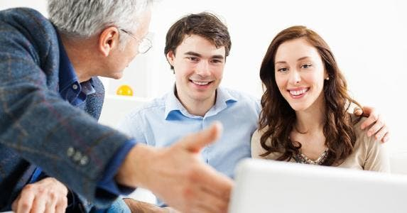 Adviser showing data to young couple © iStock