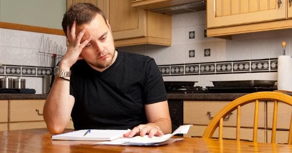 Man looking at debt at table © iStock