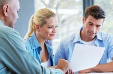 Young couple reading contract with adviser  © iStock