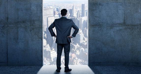 Businessman standing in open doorway to city © iStock