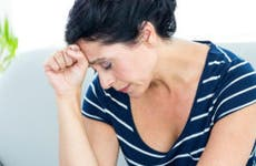 Sad woman sitting on couch © iStock