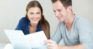 Young couple in solid beige background reading paperwork © iStock