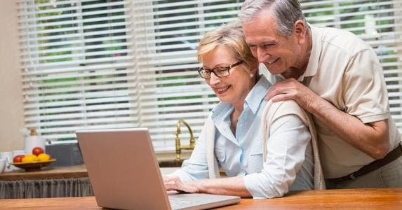 Senior couple looking at laptop together © iStock