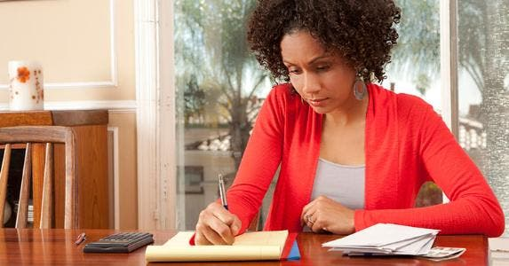 Woman on red cardigan writing down list or budget © iStock