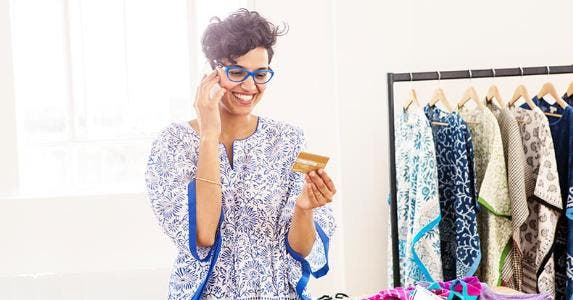 Woman smiling about her credit card | Credit: Peter Cade/Getty Images