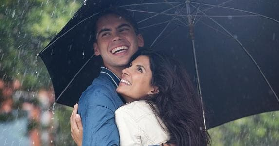 Couple laughing under umbrella in the rain | CaiaImage/Getty Images