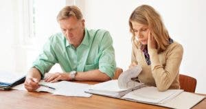 Unhappy couple looking over their finances | iStock.com/alvarez